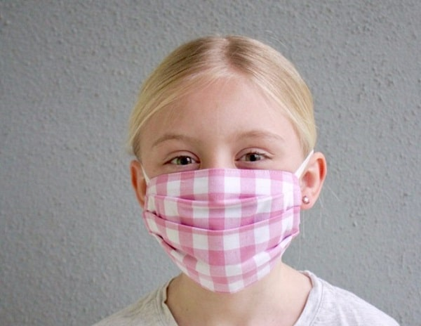 pink pleated face mask worn by child