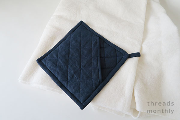navy quilted potholder placed ontop of white cotton batting