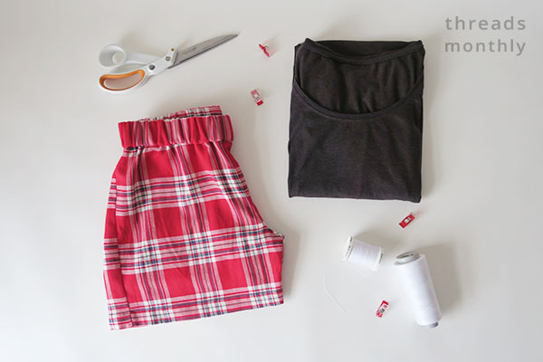flatlay of red pajama shorts, grey t-shirt, scissors, and thread.