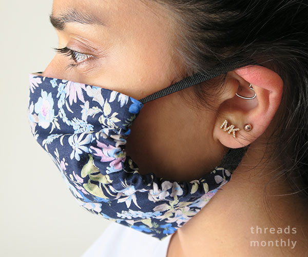 side view of a woman wearing a floral face mask with gathers