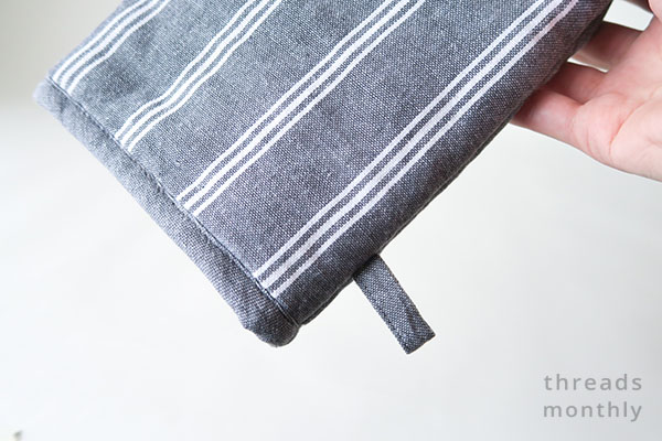 grey hanging tab on an oven mitt