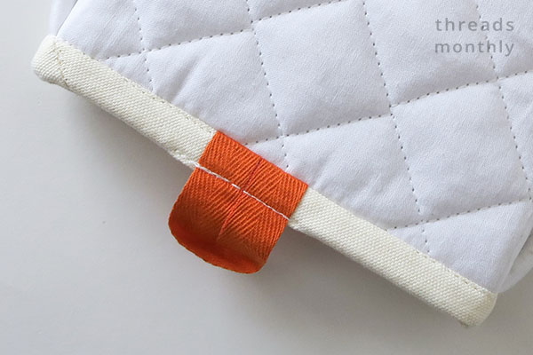 orange hanging tab on an oven mitt