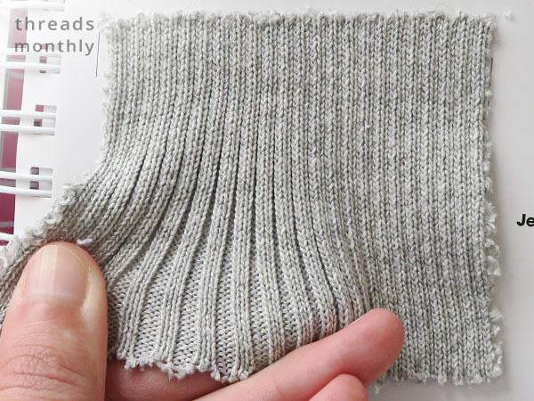 grey 2x2 rib knit fabric being stretched
