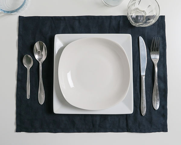 navy linen placemat with plates and cutlery on top