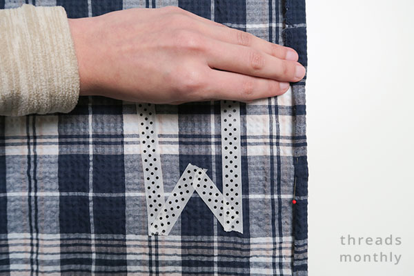 a hand turning and pinning blue check fabric