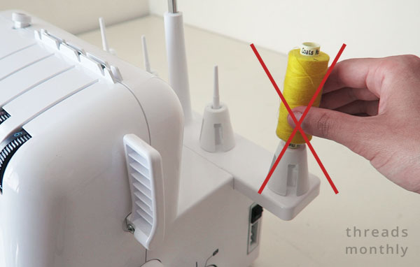 serger with yellow sewing machine thread on