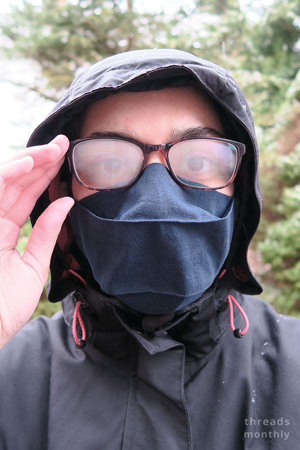 a woman wearing a 3d origami face mask and glasses that have fogged