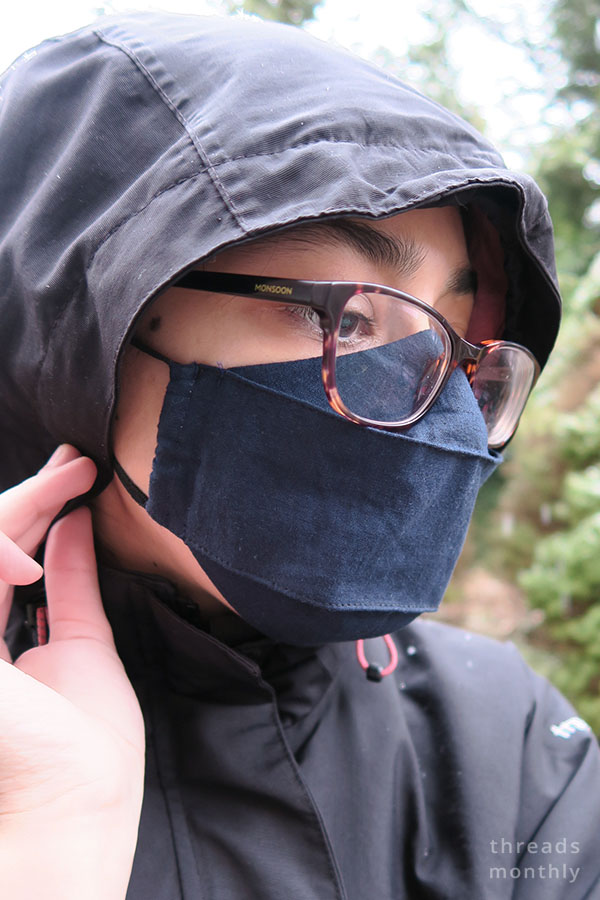 a woman wearing a 3d origami face mask and glasses