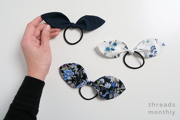 a hand holding hair bows in navy and floral prints.