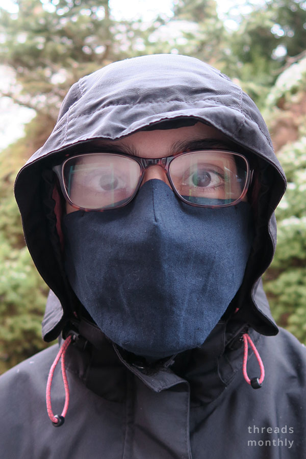 a woman wearing fogged glasses and diy face mask with darts
