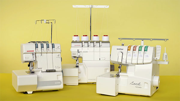 3 serger machines on a yellow backdrop