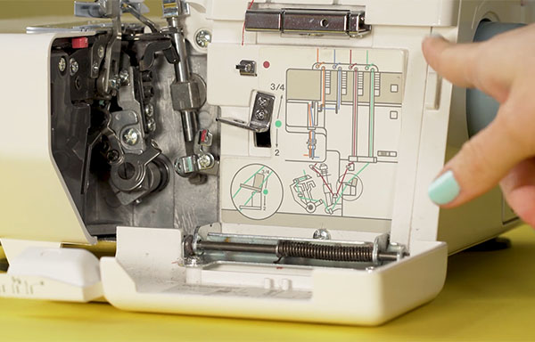 hand pointing at threading system on serger