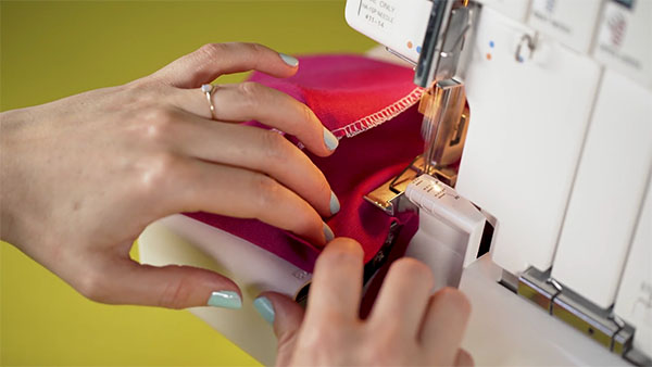 hands serging a pink tube of fabric