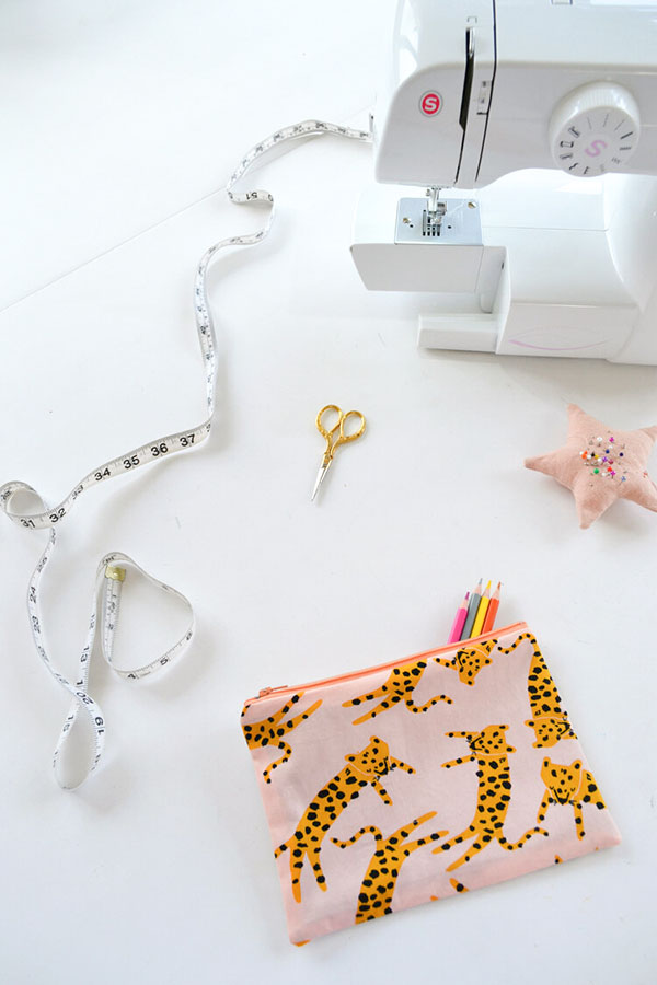 tiger print zipper pouch on a table with a sewing machine and tools