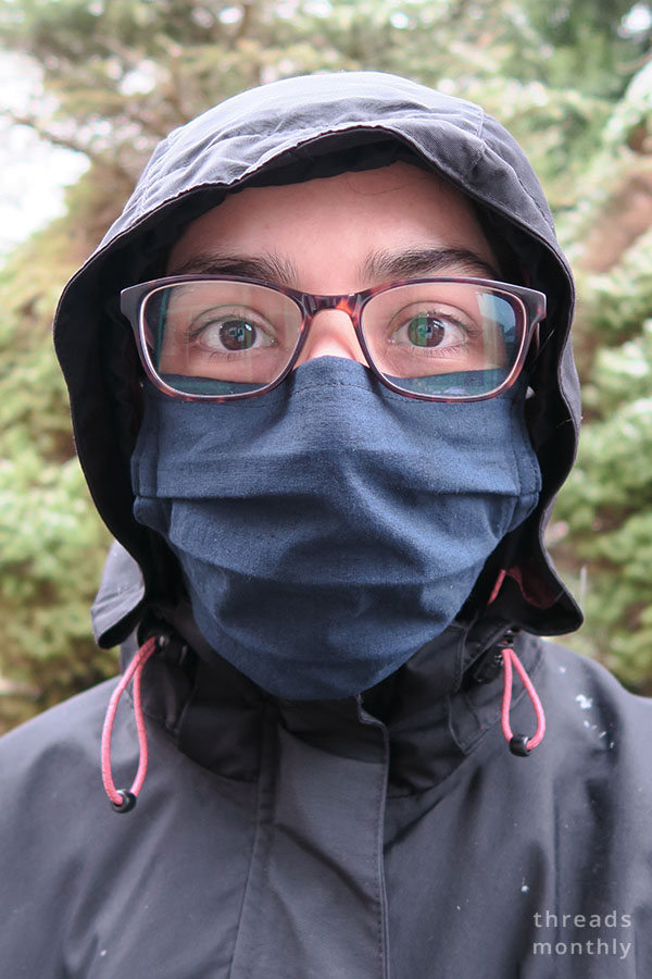 a woman wearing glasses and a pleated face mask