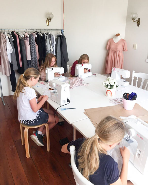 4 children learning how to sew on a machine