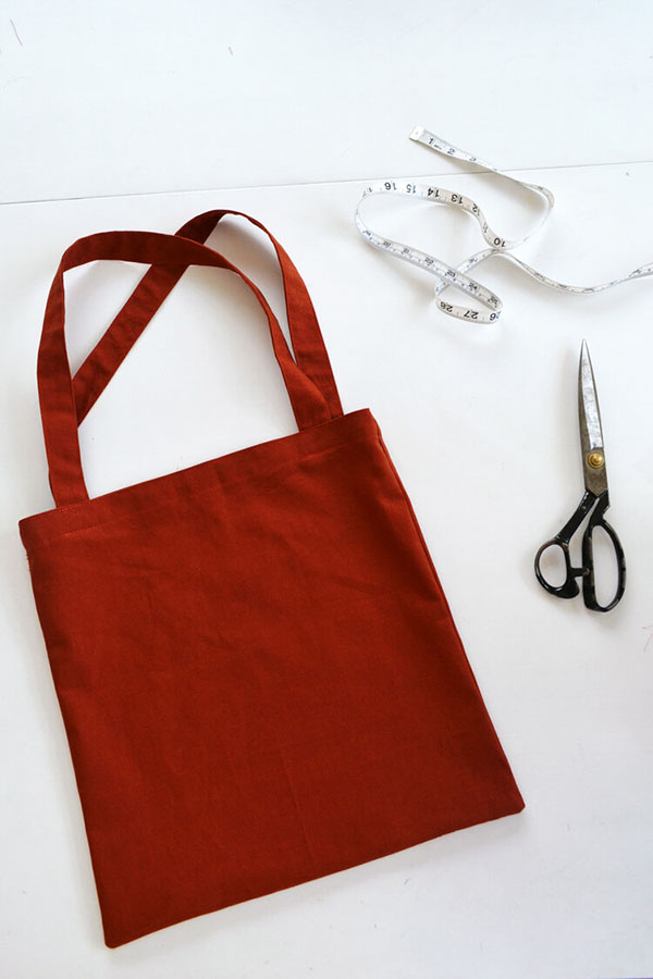red tote bag with black scissors and measuring tape