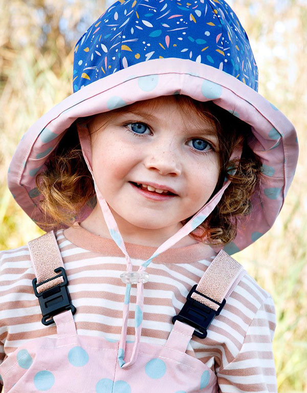 a toddler girl wearing a blue patterned bucket hat with strings.