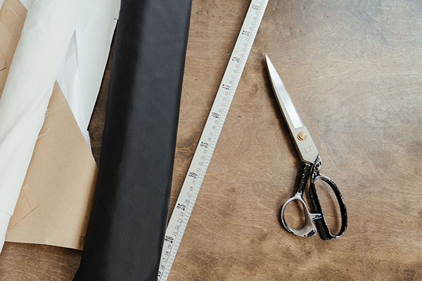 large fabric shears on a table with fabric and a tape measure.