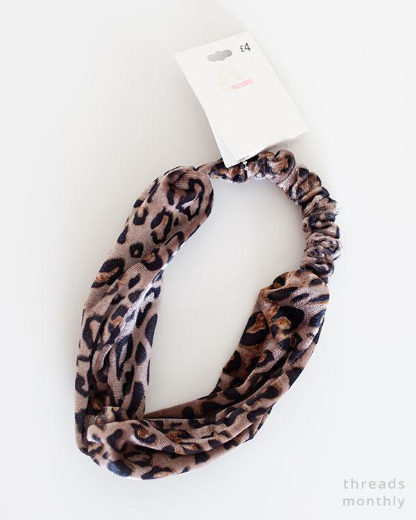 birds-eye view of a brown cheetah print turban knot headband on a white table