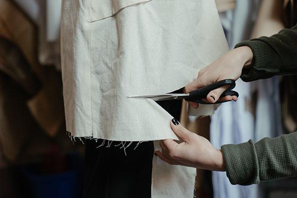 a woman cutting cream fabric with scissors.