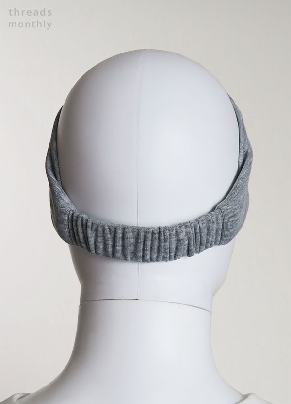 a female mannequin wearing a grey extra wide DIY headband with elastic (back view)