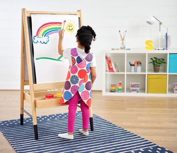 a child wearing a bright apron and painting.