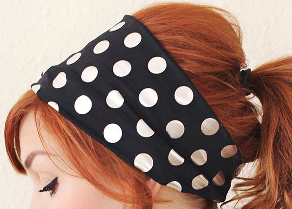 a woman wearing an extra wide stretch headband with polka dots.