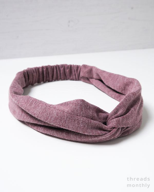 purple turban twist headband on a white table