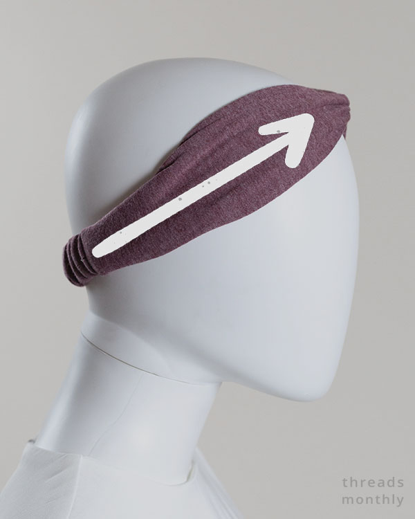 side view of a woman mannequin wearing a purple headband