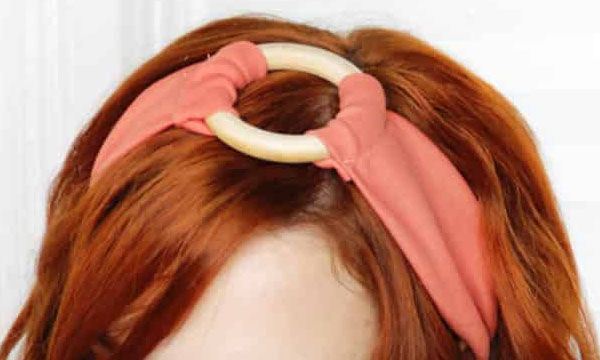 a red-headed woman wearing a DIY headband with a wooden ring in the middle.