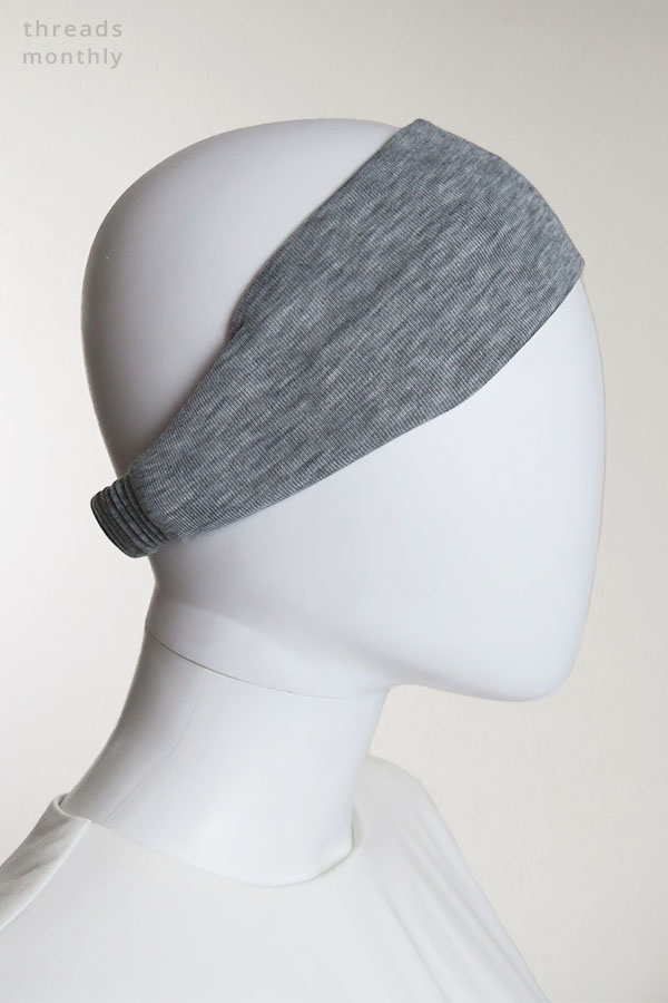 a female mannequin wearing a grey extra wide DIY headband with elastic (side view)