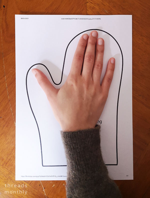 a hand ontop of a free printed sewing pattern for oven mitts.
