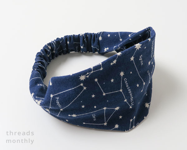 front view of an extra wide headband for toddlers with a navy star print