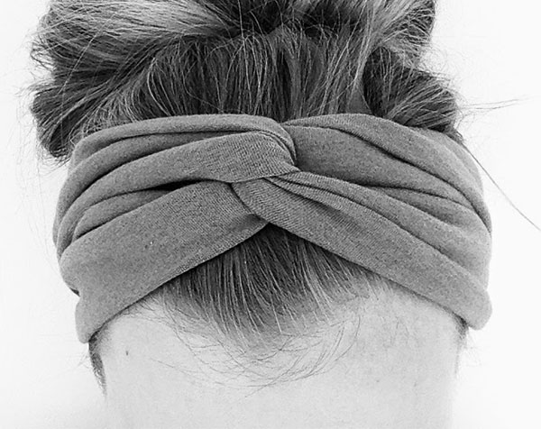 the top of a woman's head wearing a wide twist headband