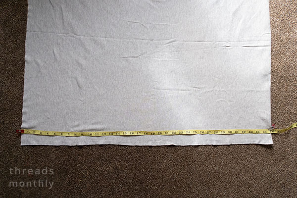 a measuring tape on top of a yard of fabric