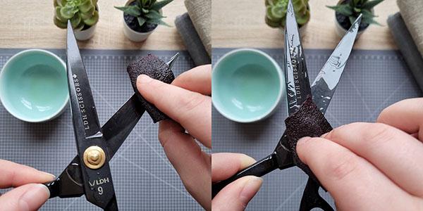 hands rubbing oil onto black fabric scissors
