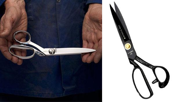 a hand holding silver fabric scissors, and a black fabric scissor.